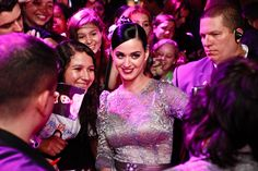 Katy Perry poses with fans for a photo.