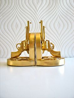 Gun Bookends in gold.  Etsy. In LOVE