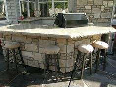 Outdoor Kitchen with natural stone finish, granite counter tops and a grill.  Looks like plenty of cabinet storage on the inside wall!