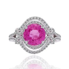Want the look of a pink diamond at a fraction of the price?  If yes, keep reading but if no, we have access to pink diamonds as well!    This stunning sapphire ring features a 2.29 carat round HOT PINK SAPPHIRE, measuring 7.9 mm.  This gorgeous stone is rare find and we made a super rare ring to honor it!  The diamonds are micropave -- handset with perfection,  E/F color,  VVS clarity, and weigh 0.52 carats in total. The total gemstone & diamond weight of the ring is 2.81 carats. All stones…