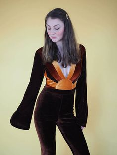 A stunning 70s inspired jumpsuit with Sunrise Detail and plunging neckline. Made in a luxurious stretch velvet fabric with a high waist, stunning bell bottoms and bell sleeves. The amazing Sunrise detail made from varying shades of velvet makes this outfit perfect for evening or