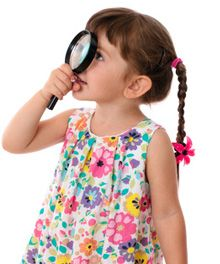 Kleines Mädchen mit Lupe auf Schatzsuche