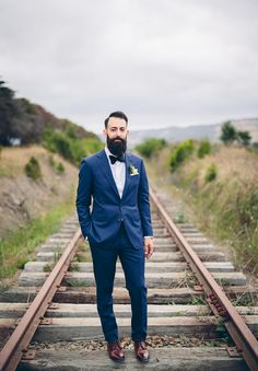 Very dapper groom with a beard wearing dark brown shoes and dark blue fitted suit with bow tie.