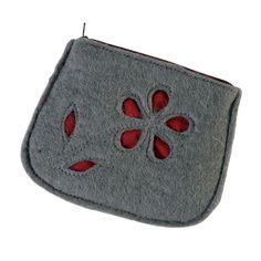 Stitched from handmade felt, this cute grey coin purse features a cutout flower design against a burgundy backing. Fashionable and Fair Trade. The purse closes with a zipper and the interior is lined with burgundy cotton.