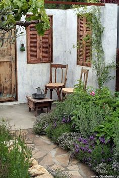 little corner patio with shutters and old chairs.