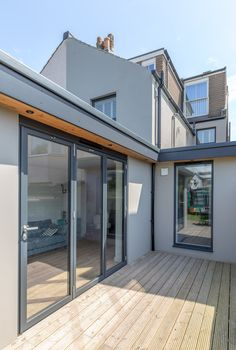 Modern bi-fold doors | floor to ceiling glazing | flat roof extension | painted grey render | flat roof overhang with spot lights |
