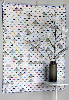 """Triangle Scraps quilt at Salty Oat. She paired white, cream, and khaki squares with little triangles of color, ranging from vintage to modern fabrics.   The pattern is """"Up, Up, and Away"""" by Amanda Jean Nyberg in the book 'Sunday Morning Quilts'."""