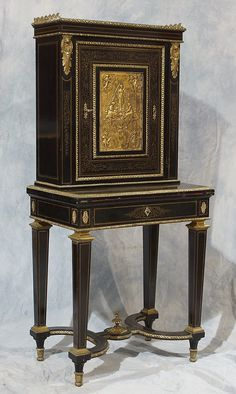 Napoleon III brass inlaid ebonized ladies desk with gilt bronze mounts, upper door with embossed ormolu panel depicting maidens and cherubs, fold over Writing Desk...