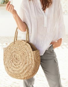 Handwoven by artisans, this natural seagrass basket bag is perfect for everything from sunny holidays to trips to the farmer's market. It has an unusual rounded shape, with a flattened base so you can still put it down when you're not carrying it by the two top handles. We've ensured no loose ends or rough edges so that the finish is smooth against skin and clothing. Handwoven 100% straw