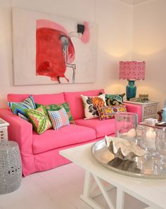 Love the art, pink sofa and colorful art offset by the neutral walls, carpet and side tables.