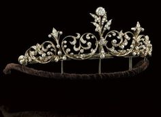 A late Victorian diamond tiara/necklace--Composed of a series of graduated openwork old brilliant-cut diamond panels of foliate design with stylised diamond foliate intersections, the back section composed of a line of old brilliant-cut diamond collets with knife-edge connections, mounted in silver and gold, approximately 36.5 cm long, circa 1890.