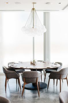 mid-century style with contemporary flair // bubble chandelier, round table and upholstered chairs create a beautiful dining space