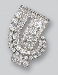 Diamond clip, Cartier, 1930s. Of stylised scroll design set with lines of circular- and step-cut diamonds, mounted in platinum.