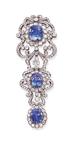 A SAPPHIRE AND DIAMOND CLIP BROOCH   Set with three cushion-shaped sapphires weighing 12.79, 17.07 and 22.18 carats, each in a rose-cut diamond surround, the top two with a rose-cut diamond scrolled frame