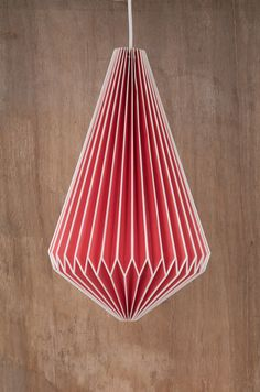 This paper lampshade is handmade from red paper in the city of Jaipur.