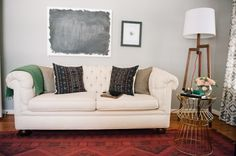 Off white tufted sofa, grey accessories with red and turquoise