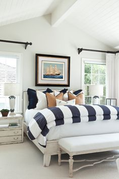The perfect guest room, beach themed, sailboat art, striped comforter, bed bench, shabby chic bedside tables | Barclay Butera Interiors