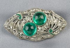 Art Deco Platinum, Emerald, and Diamond Brooch, set with two emerald cabochons within a pierced mount, further set with old mine- and rose-cut diamonds, lg. 1 3/4 in