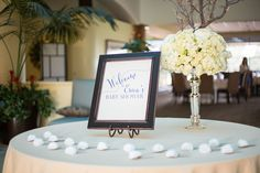 You're Welcome Events Baby Shower at SeaCliff Country Club in Huntington Beach, CA. Welcome table at foyer with cream floral spray with manzanita branches and white felt floral lapel pins and welcome sign