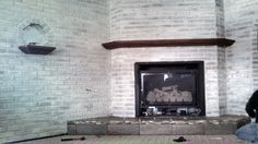 Refaced ugly fireplace...for under $100.  White wash faux brick, re-tiled hearth with floor tile and back splash accent, stained the existing wood.