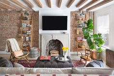 Love that this feels really lived in. Great exposed beams, exposed brick and mix of cozy textures. Also great use of a quilt.