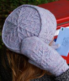 Let It Snow by Caroline Levander. This hat and mitten set features snowflake patterns created with cable stitches on a background of reverse stockinette stitch, accented with applied i-cord bands.