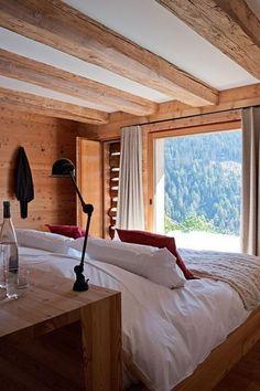 Poutres en bois brut et mobilier vintage pour cette chambre