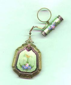 """Enameled Vanity """"tango"""" purse with an engraved finger ring, an attached compact with mirror and a separate lipstick. The back is etched with a floral design and the chain has little embossed links."""