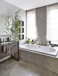 Také koupelna dokonale odráží zenovou náladu prostředí, je velmi útulná, ale střídmá. Betonová stěrka je kombinovaná s velkoformátovou dlažbou imitující beton. Jejich surovost zjemňuje dřevěný nábytek, sladěné doplňky a rostliny v asijském duchu. K většímu komfortu přispívá i vana pro dvě osoby.