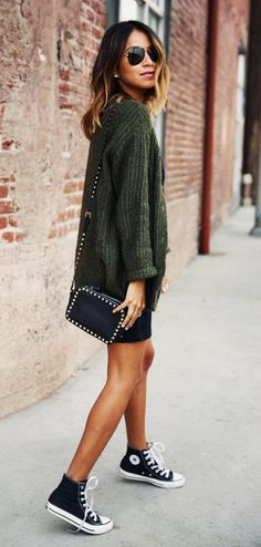 Julie Sarinana of Sincerely Jules in a cute casual knit with a black mini skirt and Converse high-tops