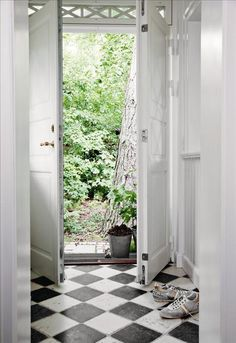 Redan i entrén slås tonen an: schackrutigt golv mot högblanka pärlspontspaneler och spegeldörrar.