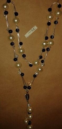 Collar largo, perlas y cuentas negras y un toque en plateado....