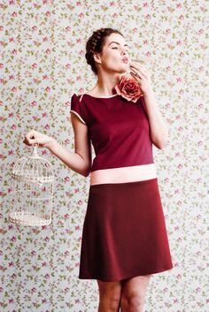 Labude - Kleid Germaine ist ein bordeauxrotes, ausgestelltes Kleid aus weich fallendem Jerseymaterial mit großer, zartglänzender Blüte am Ausschnitt