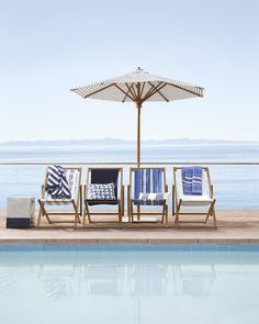 Blue and white outdoor teak sling chairs by the pool