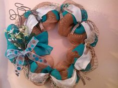 Light brown deco mesh wreath with teal and white burlap ribbons. The fun teal and brown ribbon used for the bow is a personal favorite!