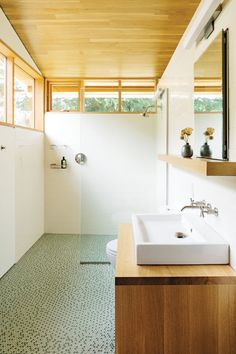 In this bathroom, the light timber complements the spa-like penny flooring tiles and white sink
