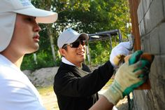 Actor Jet Li working with a volunteer on a Habitat for Humanity house.