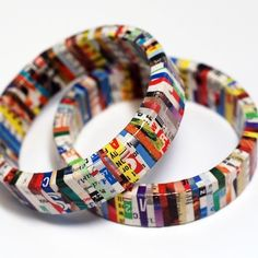 Use a shredder to shred magazines.  Glue each shred to a wooden bracelet.  Finish with clear gloss (could use clear nail polish).  Recycled Magazine Bangles