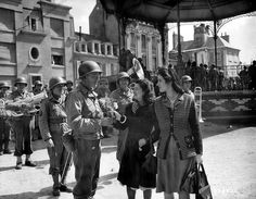 July 14, 1944. Two young French women give flowers to an American officer in Cherbourg.The Battle of Cherbourg was part of the Battle of Normandy, fought immediately after the successful Allied landings on June 6, 1944. American troops isolated and captured the fortified port, which was considered vital to the campaign in Western Europe, in a hard-fought month long campaign.