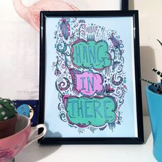 Hang in there! This cute wall art is the motivational quote you never knew you needed.  Hang it by your door. Put in your desk. Take it to the gym. It works in many situations.  A little bit more about the print:  Its A5 Hand drawn, digital coloured & printed Epson Enhanced Matte Paper, 192g/m² Blues, greens, pinks and purples - all great colours really Delivered to you in a card backed envelope Naked print! (No frame included)  ✮ ✮ Important✮ ✮ As you can see this is a colour print ...