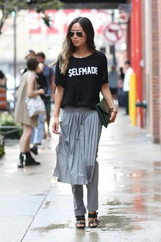 "How to Layer a Skirt Over Pants or a Dress - pleated ""skirt"" layered over gray trousers and styled with a casual graphic t-shirt + strappy sandals"