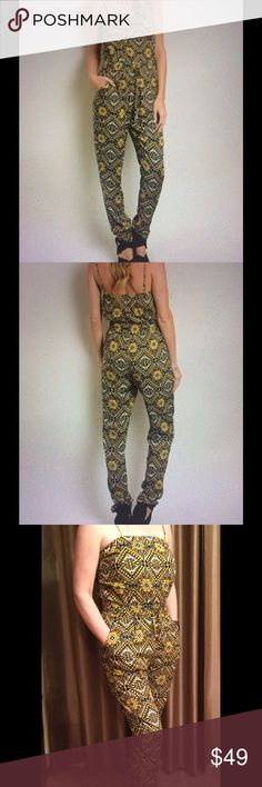 Tribal print jumpsuit in various sizes. Tribal print jumpsuit in brown/blue/gold & yellow colors. Very unique design. Truly a one-of-a-kind! Features adjustable spaghetti straps, smocked tie waist, lined top and side pockets. 100% rayon. Loose fitting makes this extremely comfortable. Just step into it. No messing with buttons or zippers! Elastic band at top.. Top is lined so no need to wear a bra! These will go fast so order yours today! This is a NWOT boutique item. No trades please. Other