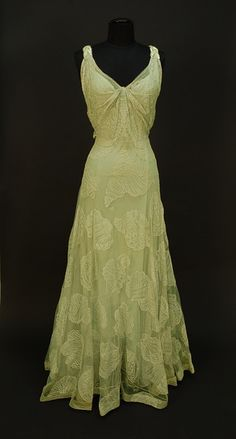 "1930s fashion, 1930s vintage fashion, WORTH NET EVENING GOWN with SEASHELL DESIGN, c. 1932. Sleeveless pale seafoam green V-neck decorated with large shells of various types, the straps with iridescent sequin decoration and scattered rhinestones at shoulder and down low back, attached seafoam crepe de chine slip, side closure. Label ""Worth"". Belonged to Elizabeth Arden, purchased from employee who received dress as a bequest at Arden's death. Bust 34, waist 25, length 61."