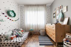 Quarto infantil com estilo escandinavo tem cômoda de pinus, parede decoradas com bolinhas adesivas e lençol estampado.