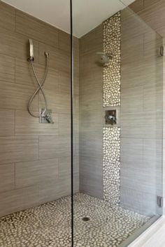 wood-like ceramic floor tile bathtub surround with river rock up around hardware