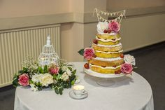 A very simple looking 3 tier, sponge Wedding cake. With strawberries, coloured icing roses and a 'Just Married' sign.