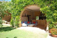 Porche abierto al jardín que se ha habilitado como zona para hacer vida al aire libre.