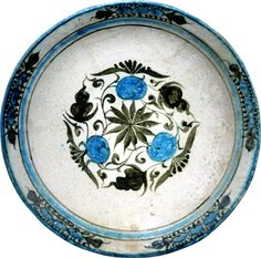 POMEGRANATES AND LEAVES - Northern Iran or Western Central Asia (Timurid), 15th century - A large pottery dish of shallow rounded form with a sloping rim standing on a short foot, the reddish buff earthenware body coated inside and partially on the outside with a white slip on which the decoration has been painted in an elegant bichrome palette of crisp black and turquoise under a transparent, colourless lead glaze with a delicate crackle.