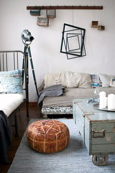 Leather pouffe in an industrial room with a metal bed via Parola Station