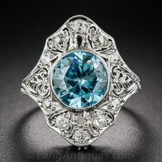 Late Edwardian Platinum Blue Zircon Ring. This enchanting late Edwardian/early Art Deco dinner ring is exceptionally designed and rendered in platinum with lacy pierced details generously studded with sparkling diamonds. The central round faceted zircon weighs in at 3.00 carats and radiates with an electric turquoise blue hue from within a finely milgrained bezel setting. Measuring 3/4 inch in length this dramatic jewel sits close to the hand and dazzles with every movement.